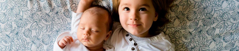 Abbildung: Baby und Kleinkind liegen auf einer Decke