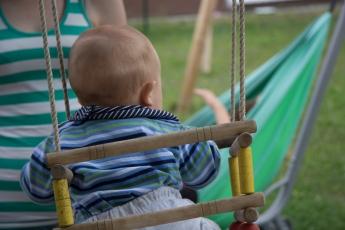 Abbildung: Baby sitzt in einer Schaukel